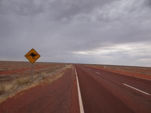 Der Stuart Highway, bedeckt von rotem Sand.