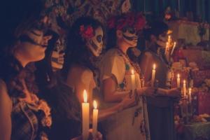 Als Catrina verkleidete Mexikanerinnen mit Kerzen vor einem Altar