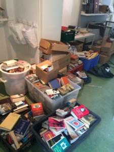Das Foto zeigt den Arbeitsplatz des Rechercheteams. Man sieht viele Bücherstapel.
