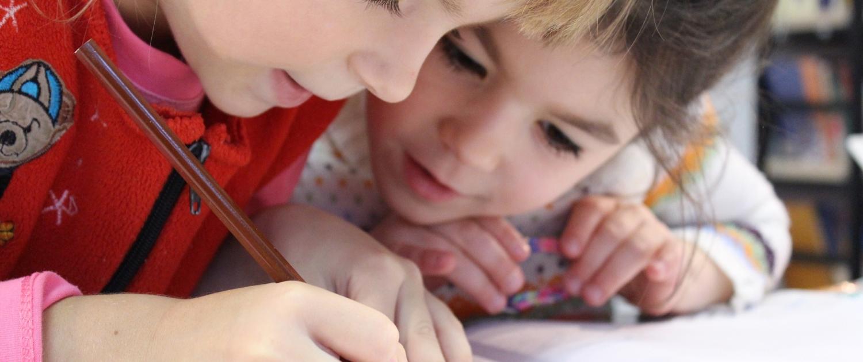 Das Foto zeigt zwei Schulkinder bei Schreibübungen