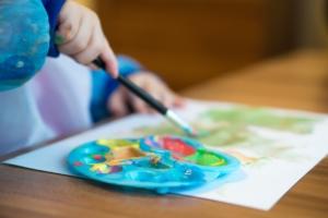Das Foto zeigt ein Kleinkind bei den ersten Malübungen auf Papier