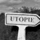 Das Bild zeigt ein pfeilförmiges Schild mit der Aufschrift Utopie